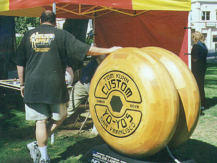Here is a photo of a man standing along side the worlds largest yo yo made by Tom Kuhn of San Francisco.
